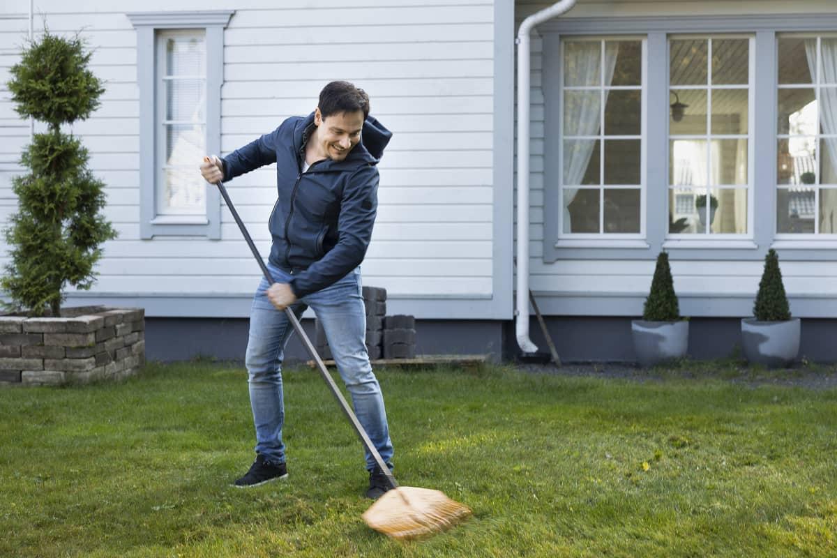 Tommi Soidinmäki haravoi nurmikkoa.