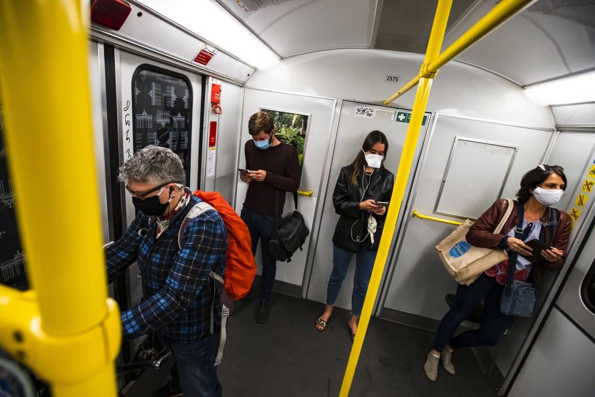 ihmisiä junassa maskit kasvoilla