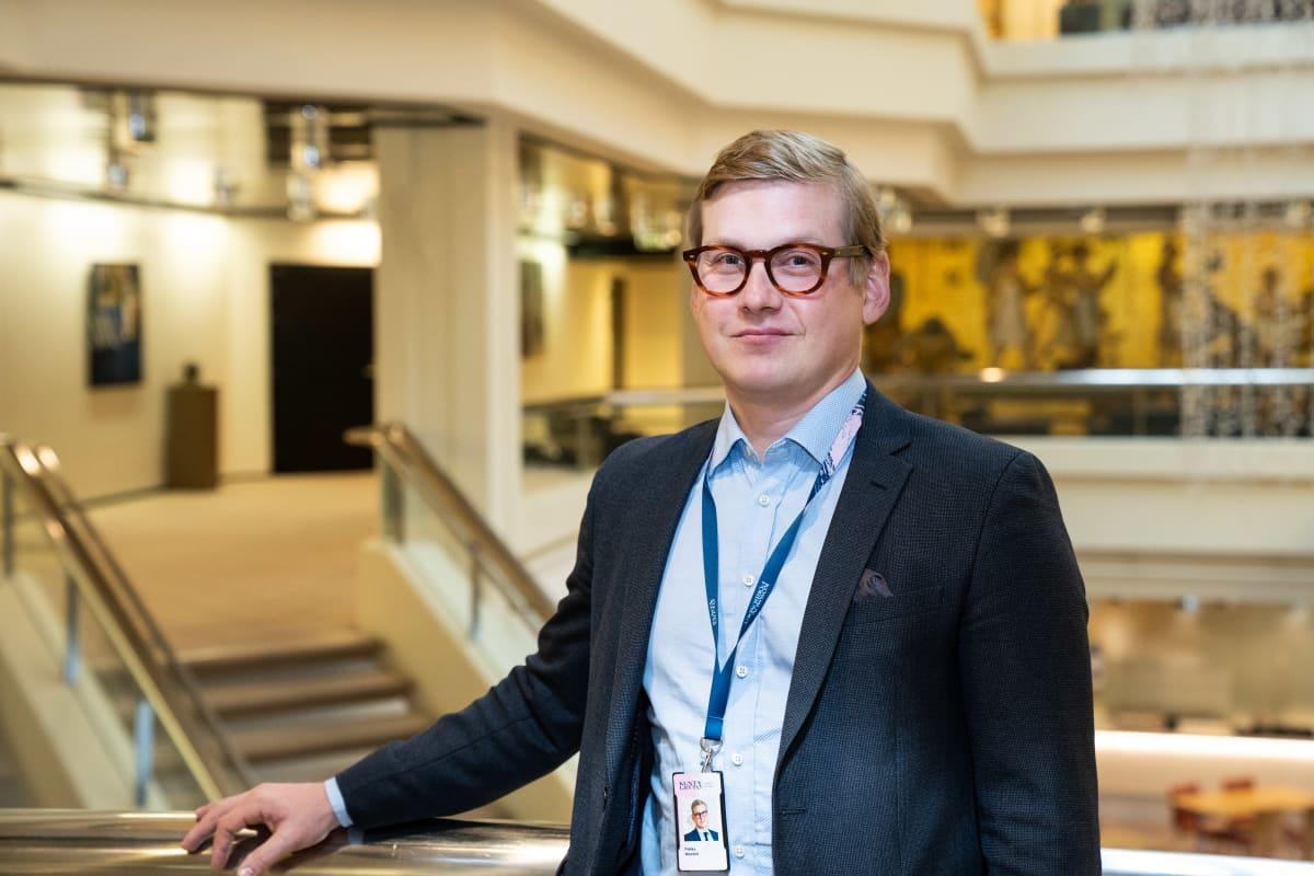 Kuntaliiton erityisasiantuntija Pekka Montell nojaa kaiteeseen Kuntatalon toisen kerroksen aulassa.