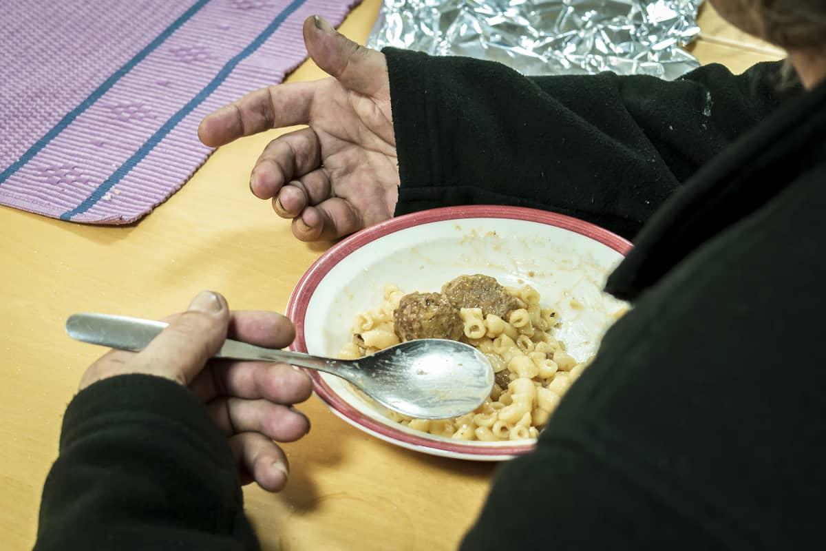 Likaiset kädet ja lautasella makaroonia ja lihapullia.