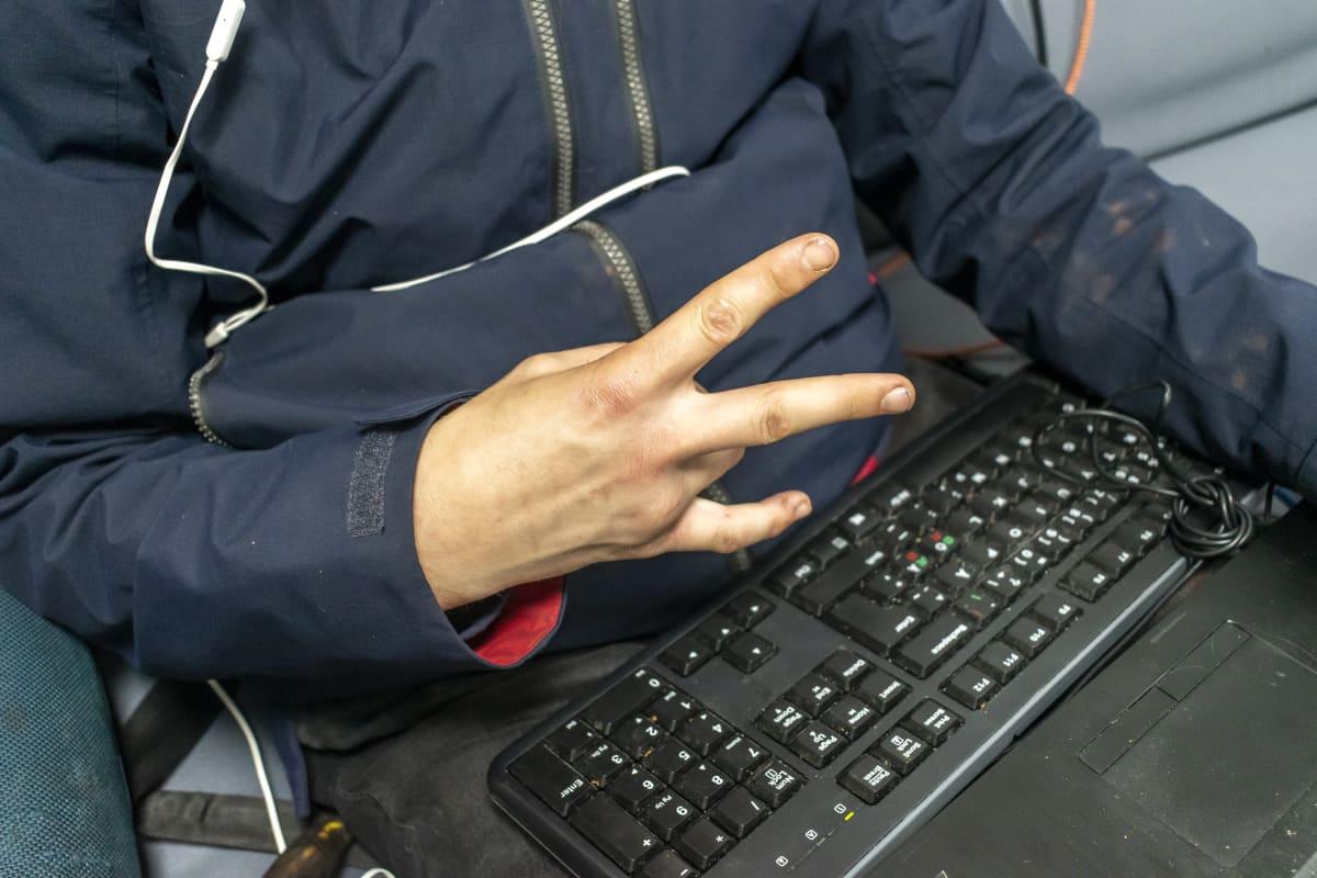Mies näyttää käsimerkkiä tietokoneen näppäimistö sylissä.