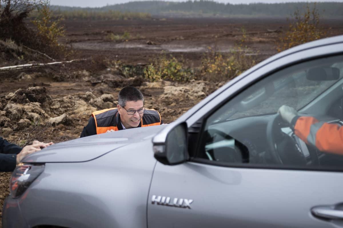 Hannu Hautala työntää turvesuohon juuttunutta autoa.