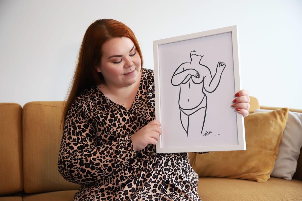 Krista Kohonen esittelemässä omakuva-taulua, joka on hänen tuttavan tekemä.