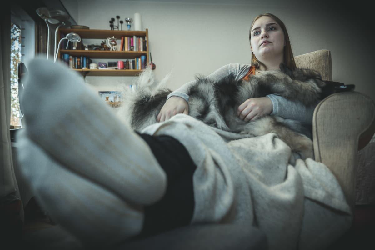 Petra Suonperä koira sylissään katsoo sohvalla kauhuelokuvaa.