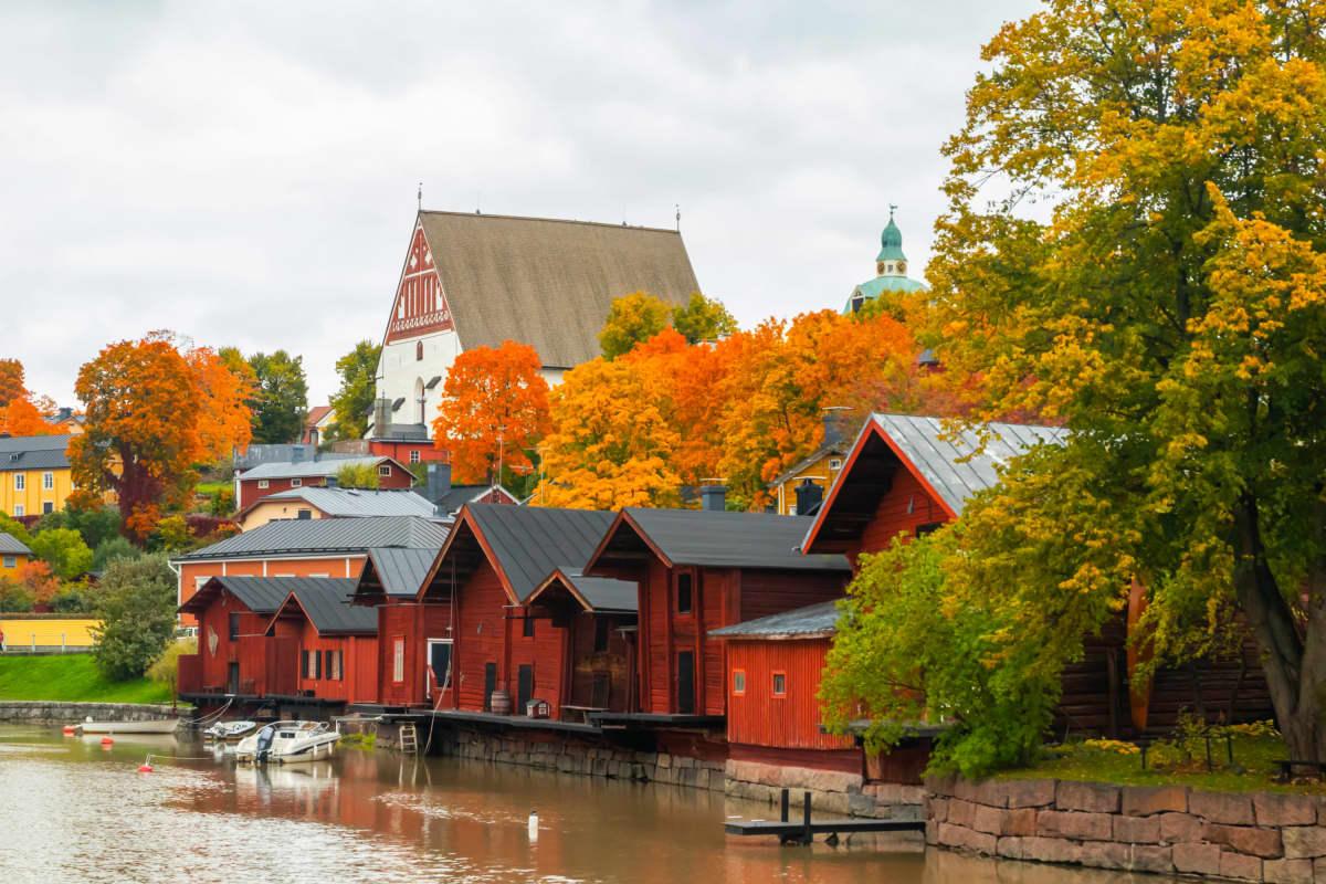 Röda bodar vid åstrand, i bakgrunden en kyrka och höstfärgade träd