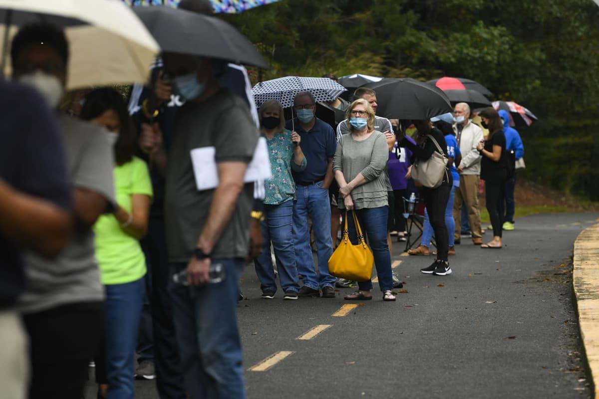 Ihmisiä jonossa. Monella on sateenvarjo.