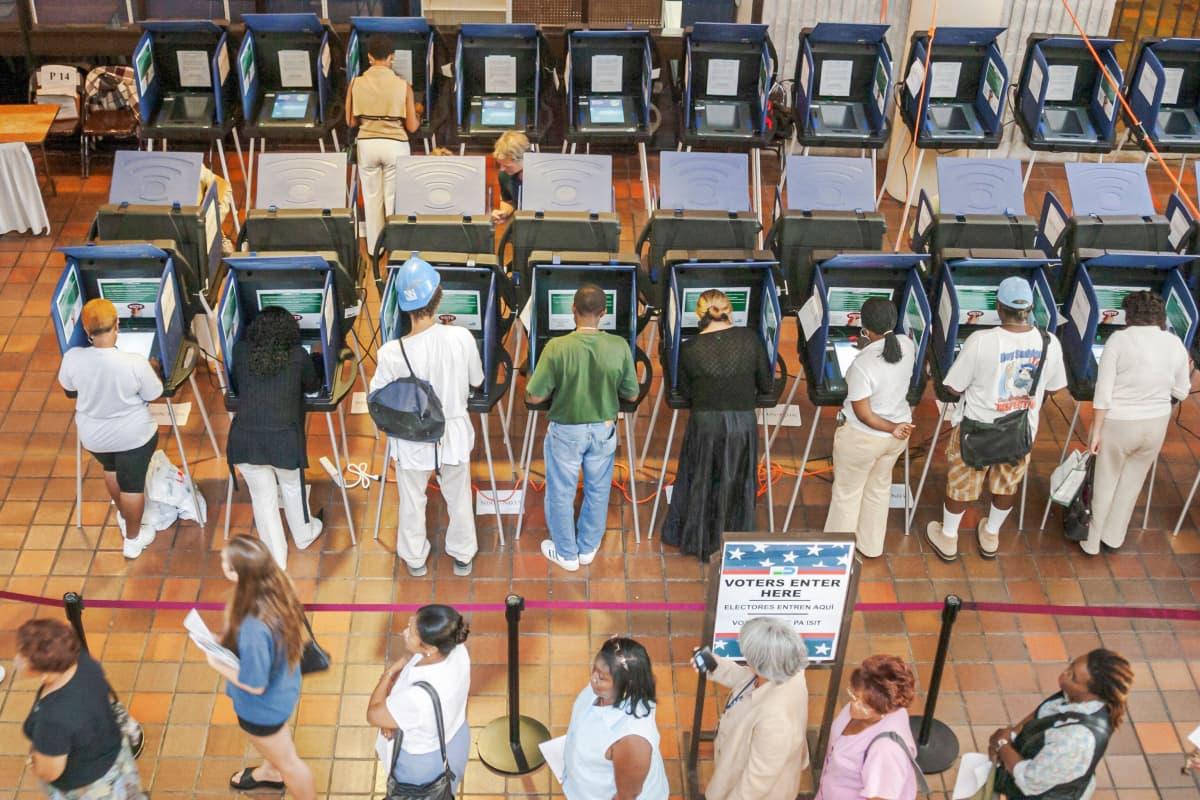 Joukko ihmisiä ennakkoäänestää äänestyskoneilla. Kuvan etualalla jonotetaan äänestämään.
