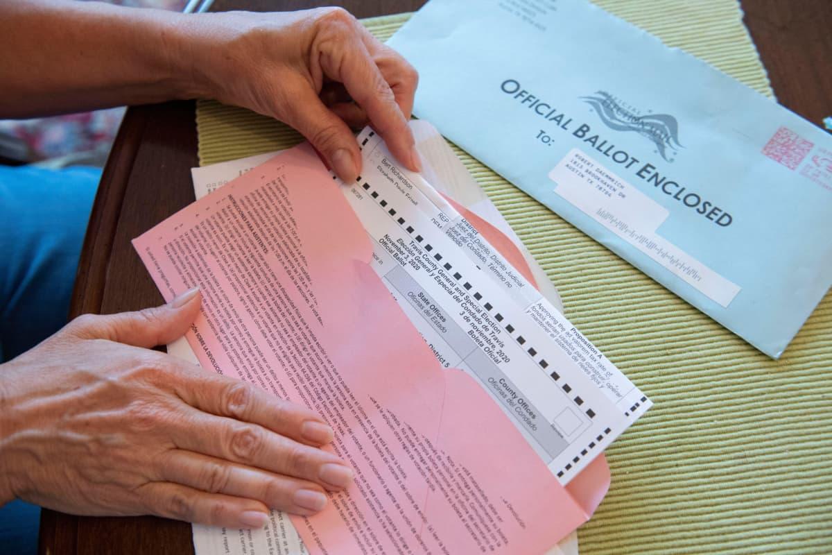Lähikuvassa nainen sulkee vaalilippua postikuoreen. Kuoressa lukee englanniksi: Official Ballot Enclosed.