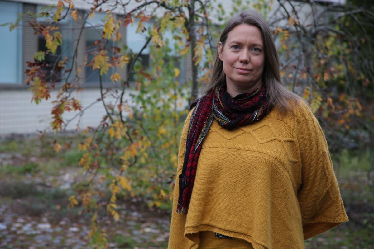 Tummahiuksinen nainen seisoo puutarhassa päällään keltainen villatakki ja punainen kaulahuivi.