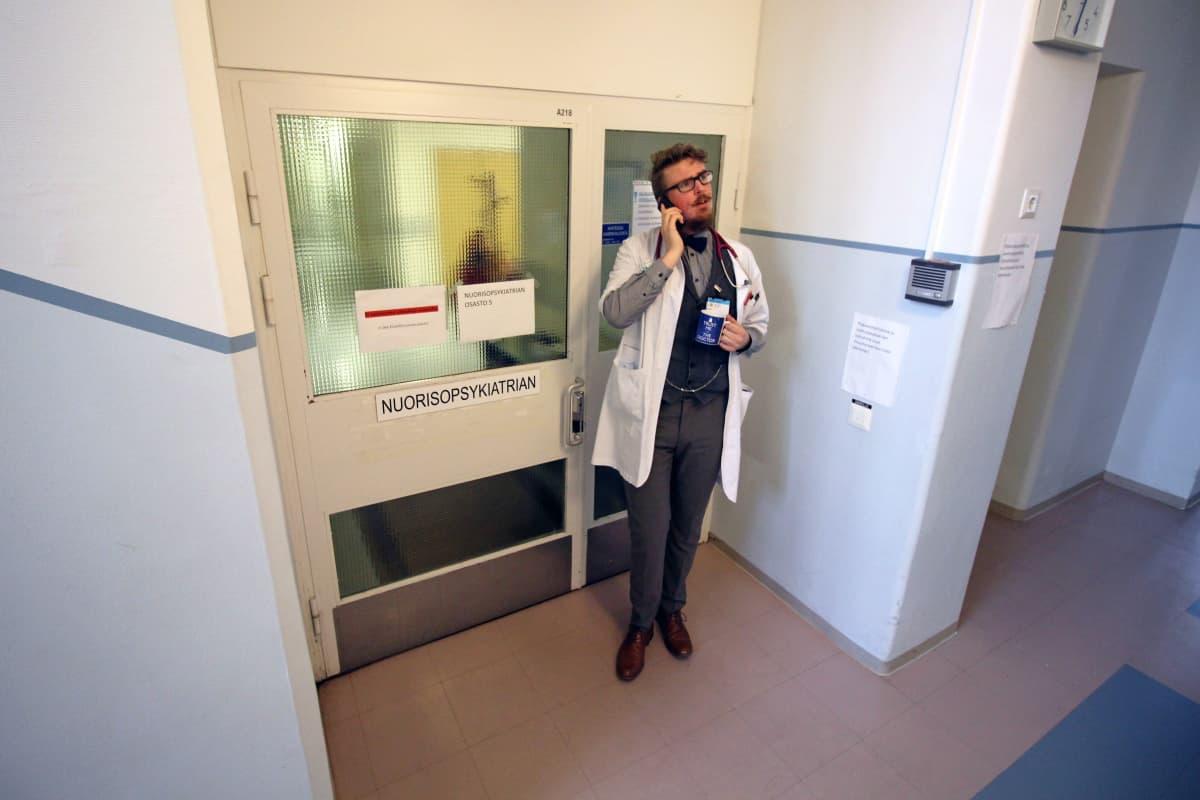Lääkäri puhuu puhelimessa nuorisopsykiatrian osaston oven edessä.
