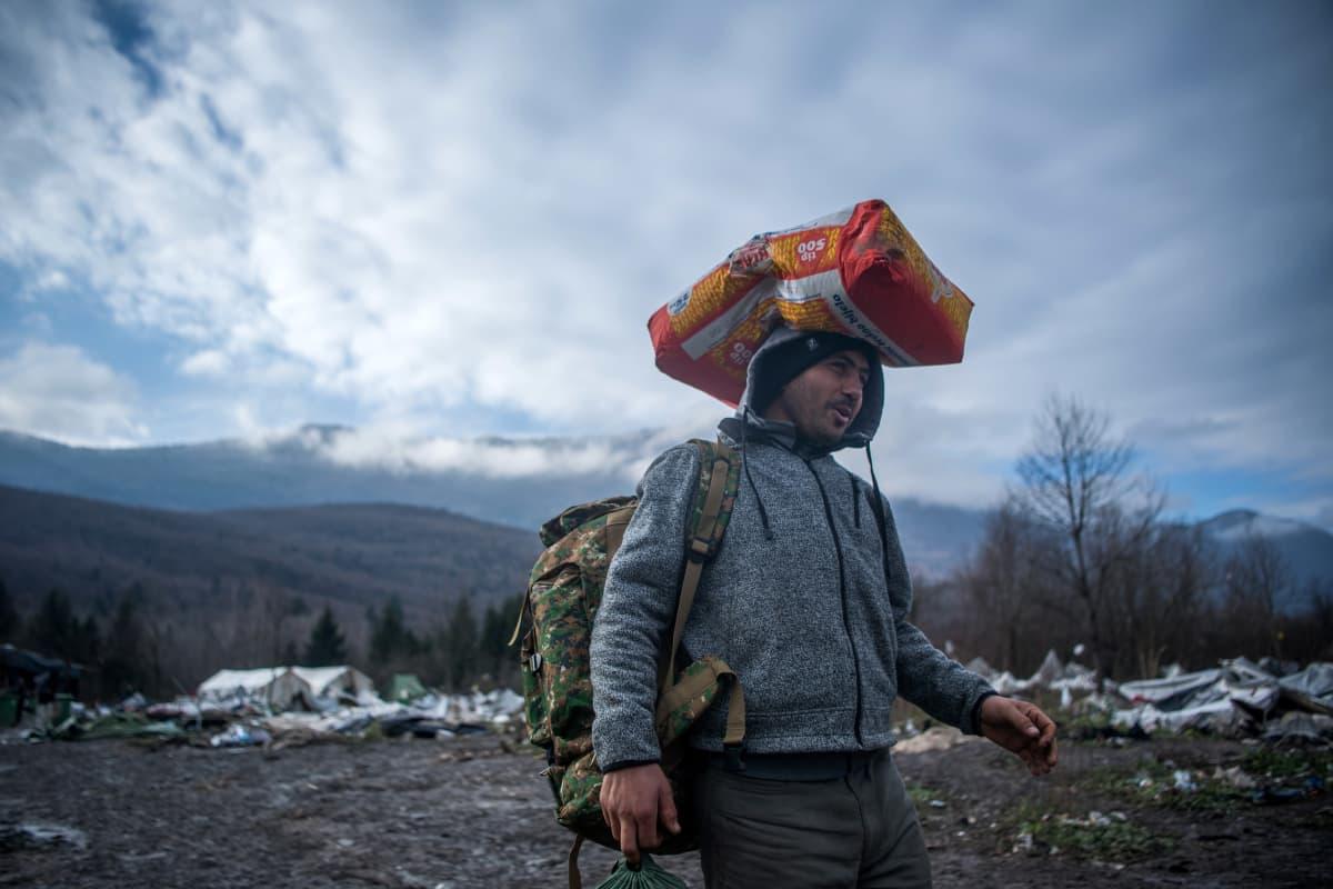 Bihacissa, Luoteis-Bosniassa, Kroatian rajan kupeessa turvapaikanhakija keräsi romua marraskuussa 2019. Läheinen Vučjakin pakolaisleiri oli määrätty purettavaksi.
