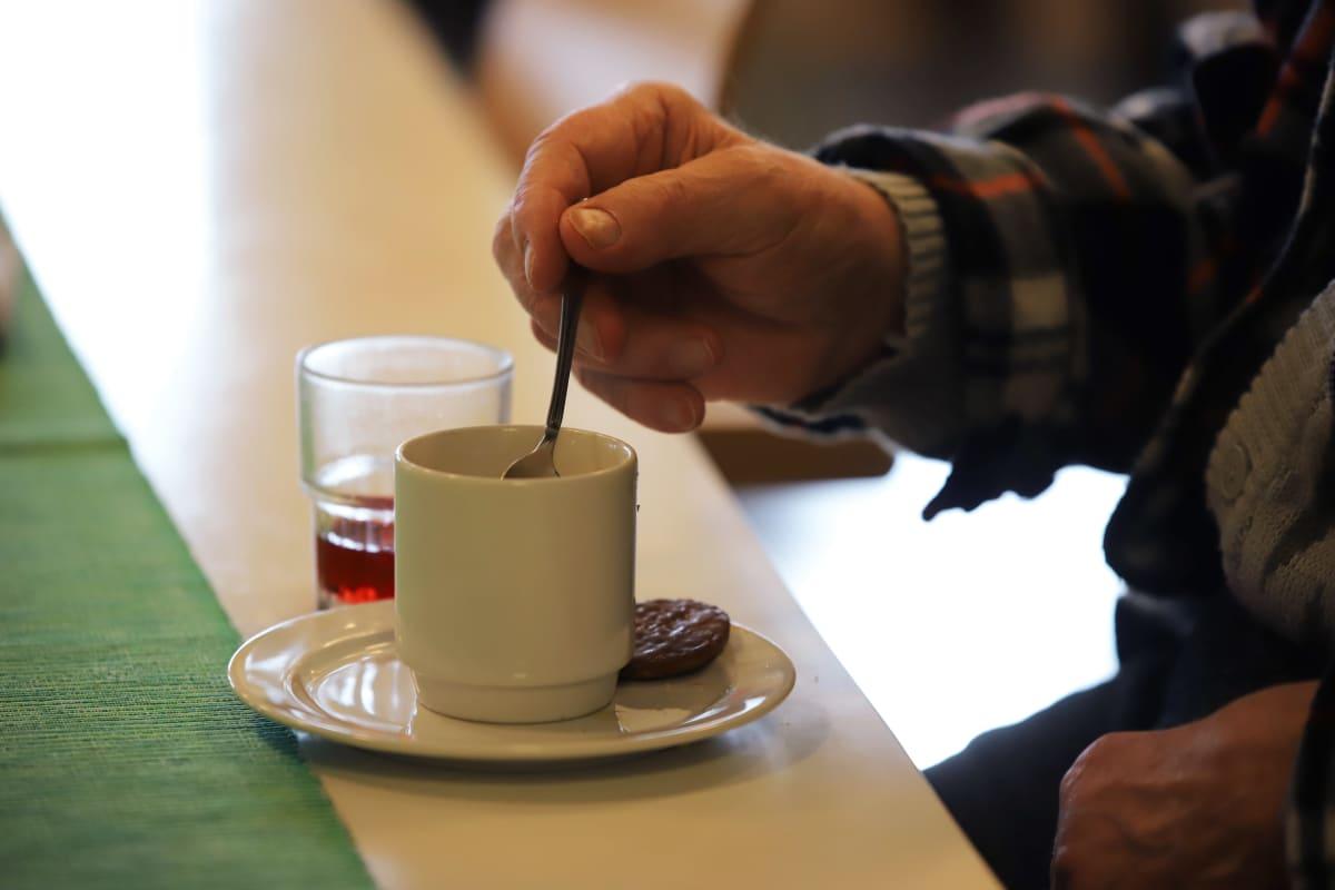 Vanhus sekoittamassa kahvia Jaalan palvelukeskuksessa.