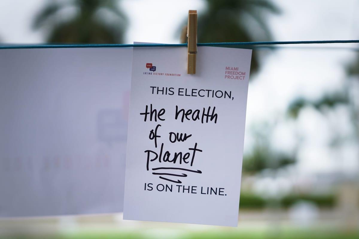 """Pyykkinarulla roikkuu paperi, jossa lukee """"The health of our Planet""""."""