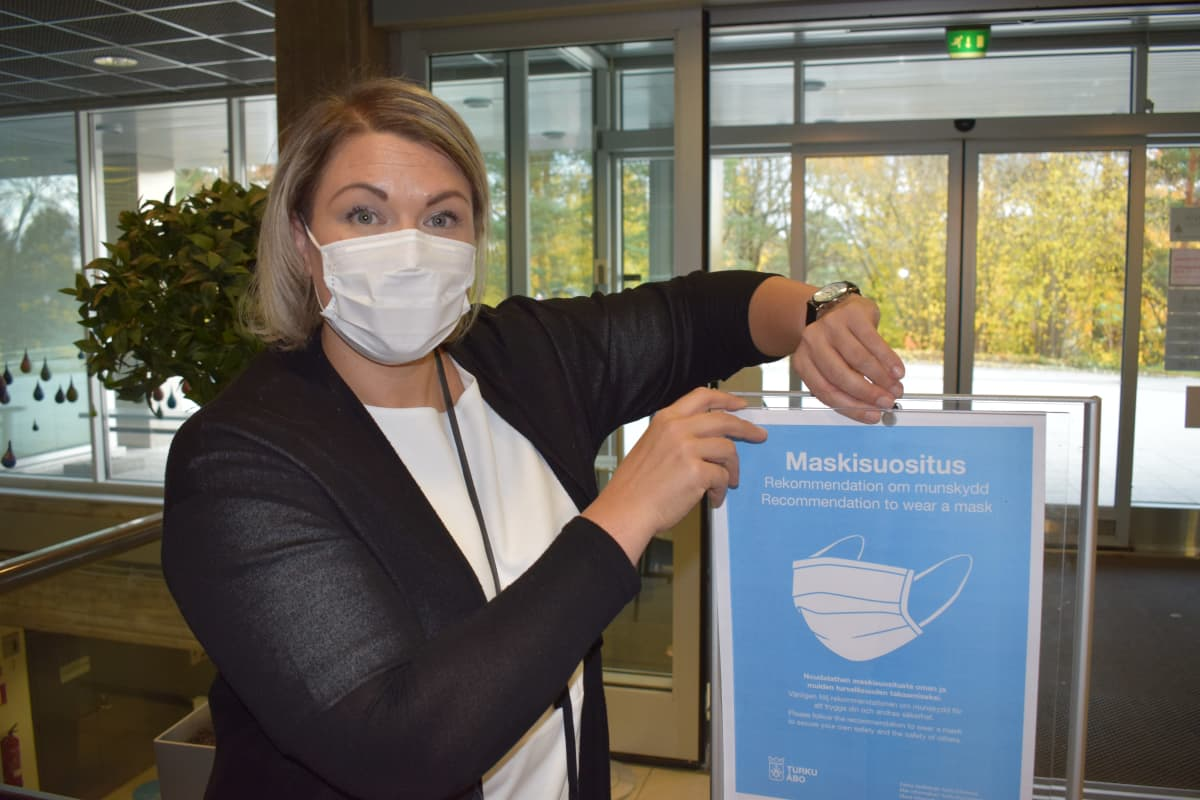 Turun kaupungin uimalaitosten päällikkö Eeva Haapanen näyttää kasvimaskisuosituskylttiä.