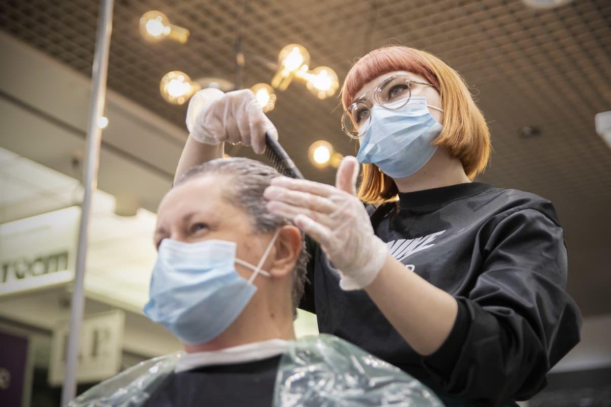 Parturi-kampaaja Sini Pieviläinen levittää väriä Sari Leinosen hiuksiin. Molemmilla on kasvomaskit yllä.