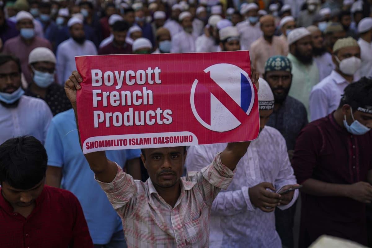 Mielenosoittaja pitelee julistetta, jossa vaaditaan englanniksi ranskaaistuotteiden boikotointia.