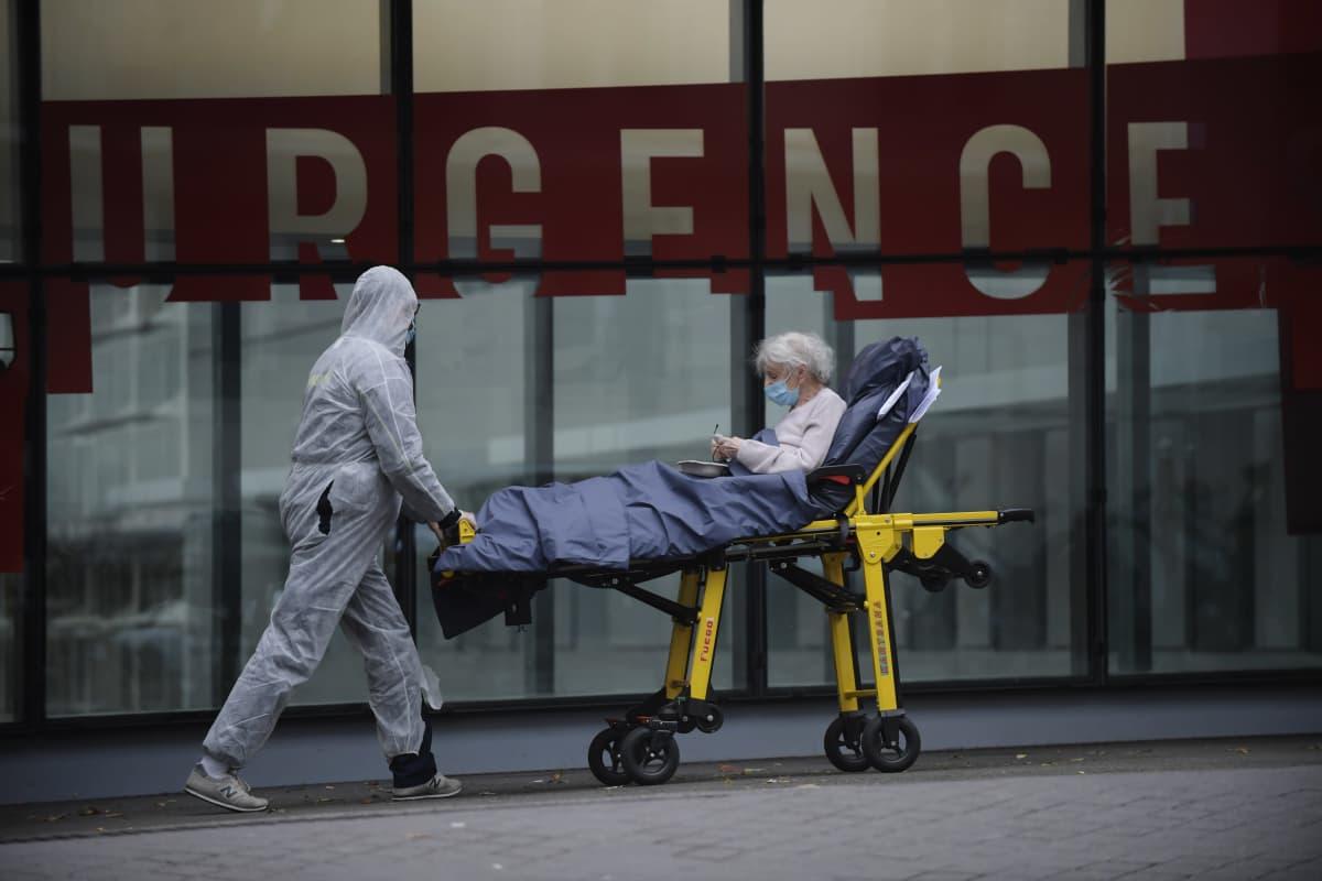 Suojapuvulla varustettu hoitohenkilökunnan edustaja kuljetti paareilla potilasta pariisilaissairaalassa keskiviikkona.
