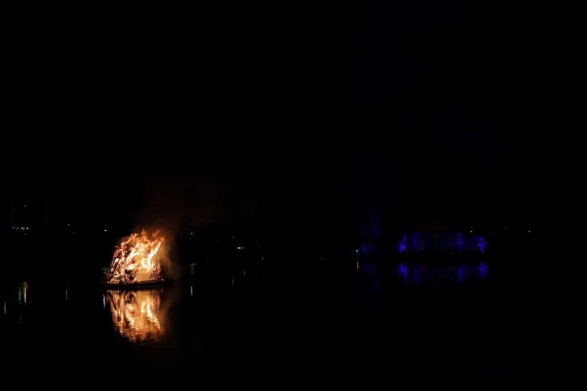 Kekripukki palaa Kajaaninjoessa, taustalla näkyy linnanrauniot sinisessä valossa.