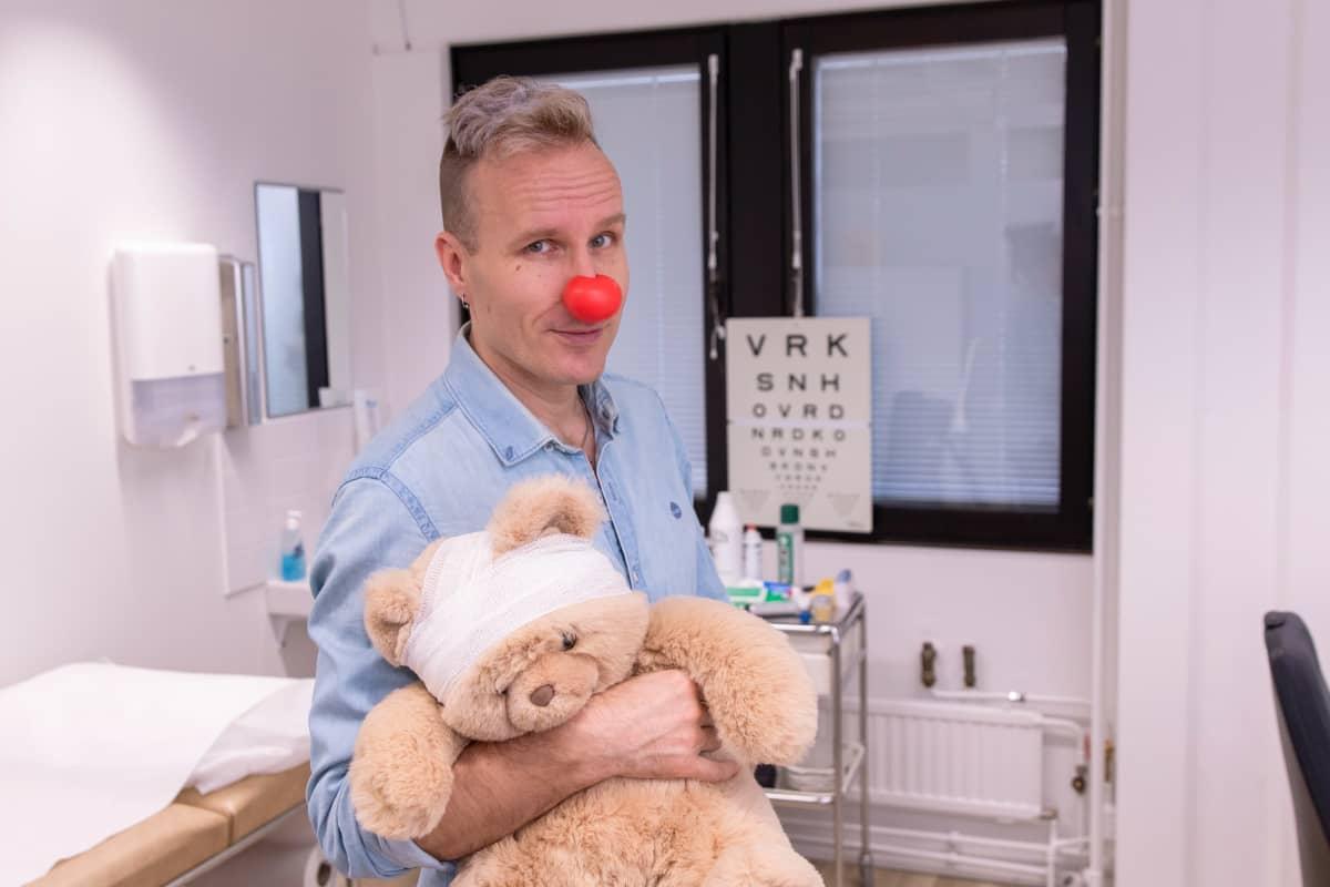 Puoli seitsemän -ohjelman juontaja Mikko Kekäläinen lääkärissä nalle sylissään, Mikolla on punainen Nenäpäivä-nenä.