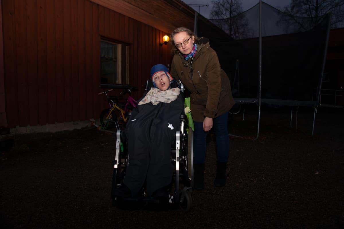Omaishoitaja Dorota Kyntäjä kotipihalla kehitysvammaisen Luukas-poikansa kanssa
