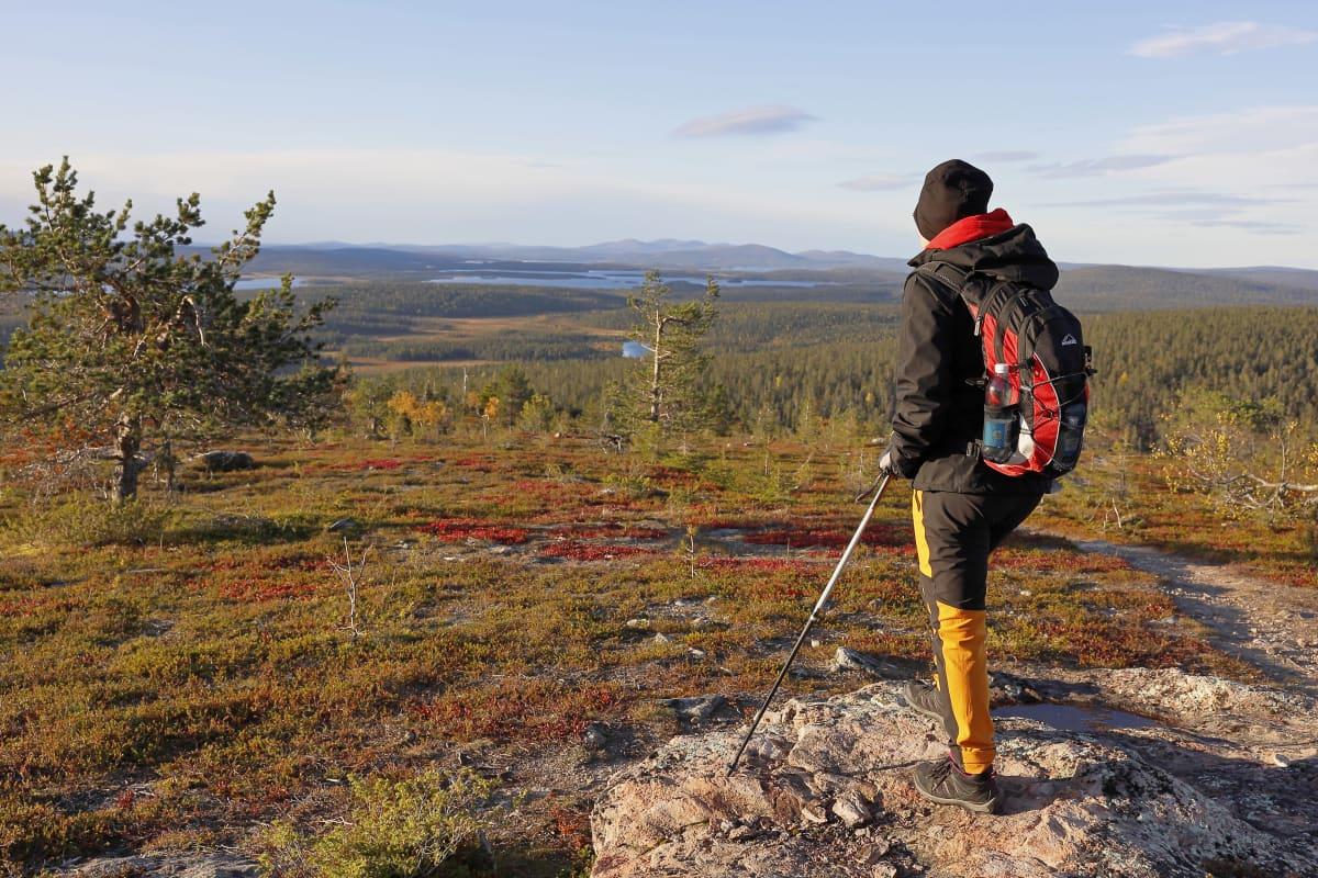 Retkeilijä Muonion Äkäskerolla, Ylläs-Pallastunturin kansallispuistossa maaruskan värittämässä maisemassa.