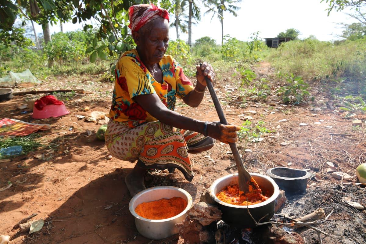 Waata-nainen valmistaa ruokaa padassa.