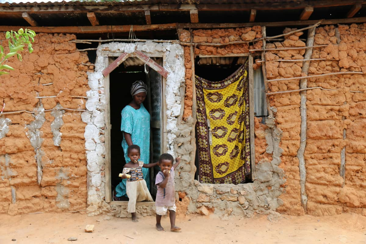 Waata-perheen talo ja lapsia.