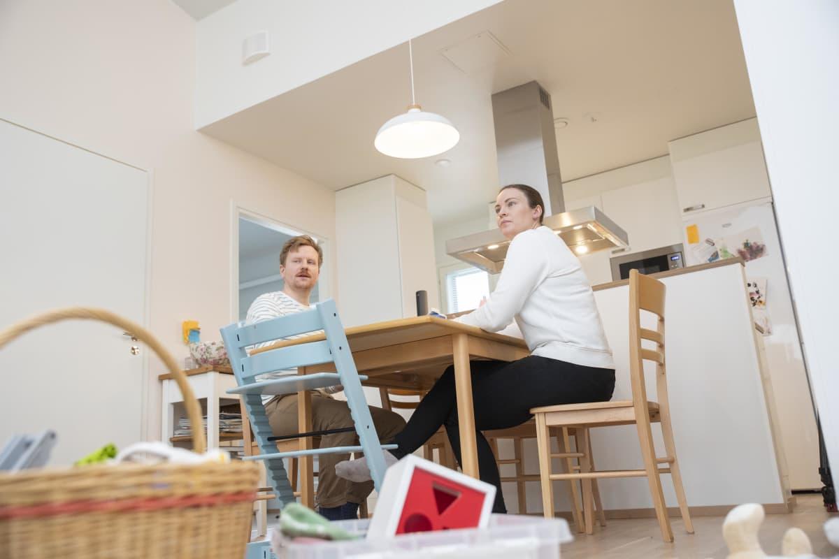 Ville Valkonen ja Minna Heinäheimo-Valkonen istuvat keittiönpöydän ääressä.