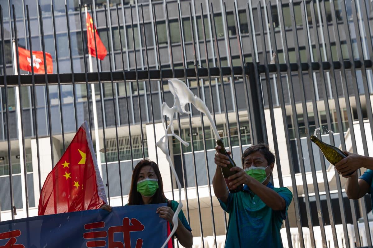 Opposition kansanedustajien lähtö sai osan juhlatuulelle lainsäädäntöneuvoston rakennuksen edustalla Hongkongissa 12. marraskuuta.