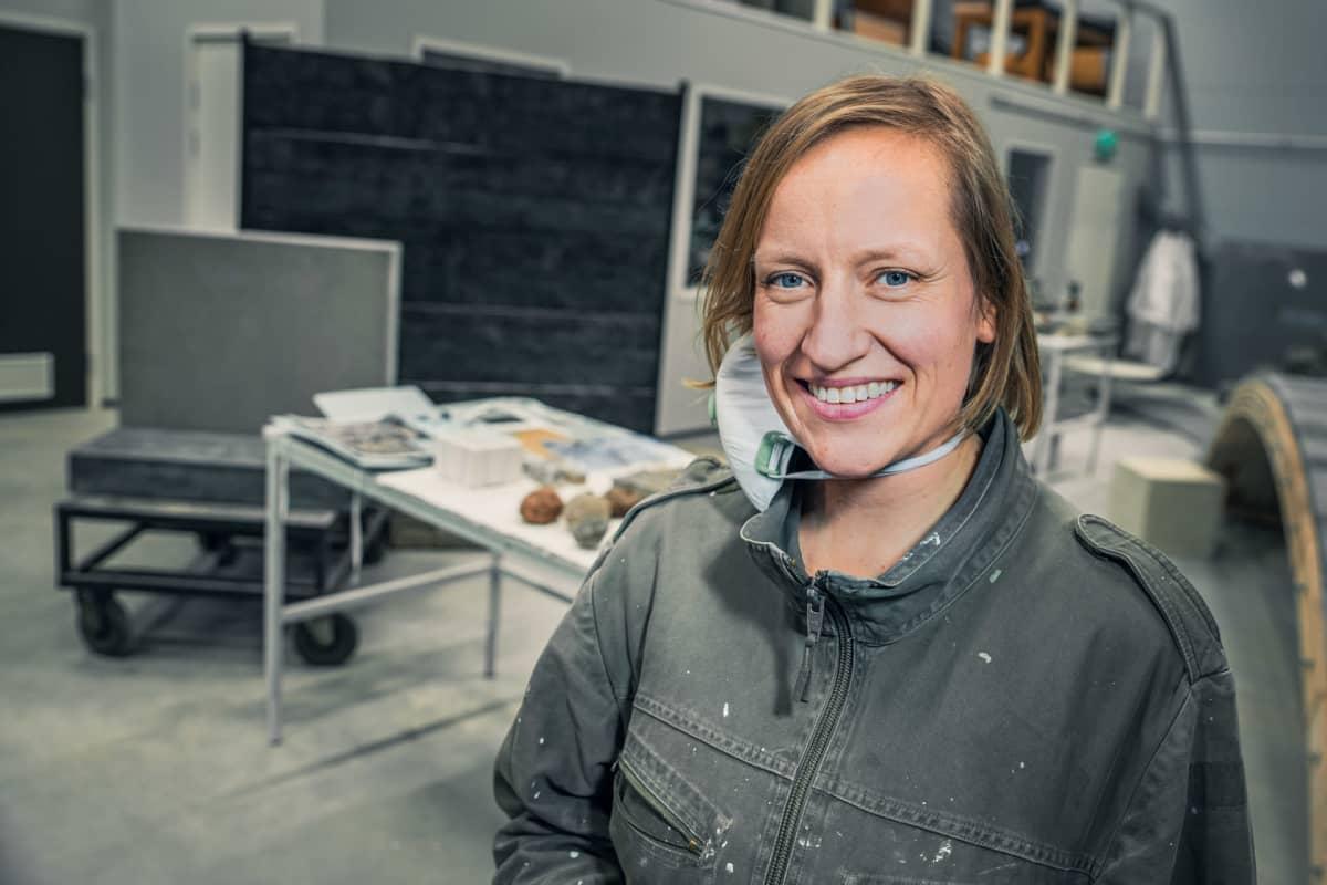 Taiteilija Maija Savolainen poseeraa työpisteensä edessä.