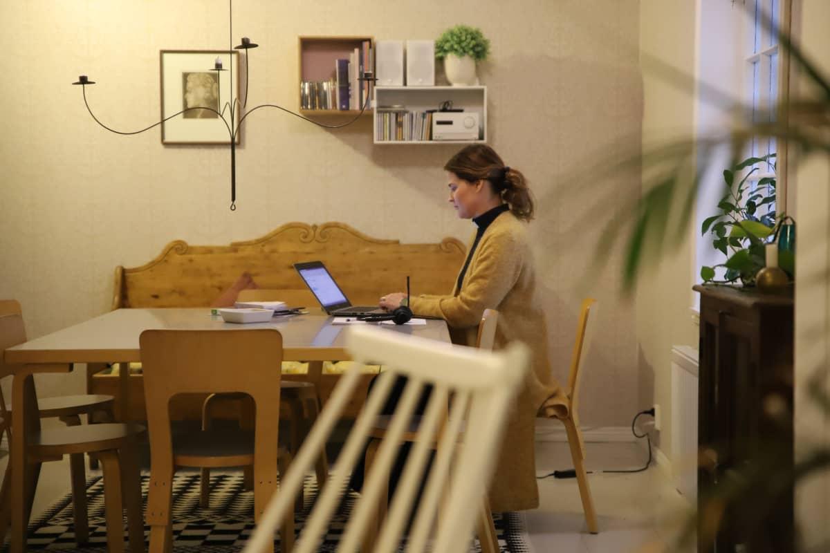 Nainen tietokoneen äärellä työpöydällä
