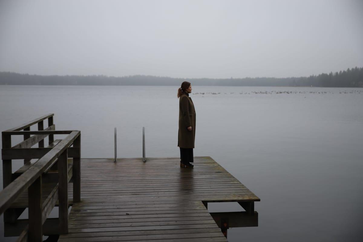 nainen seisoo laiturilla, katselee sumuiselle järvelle