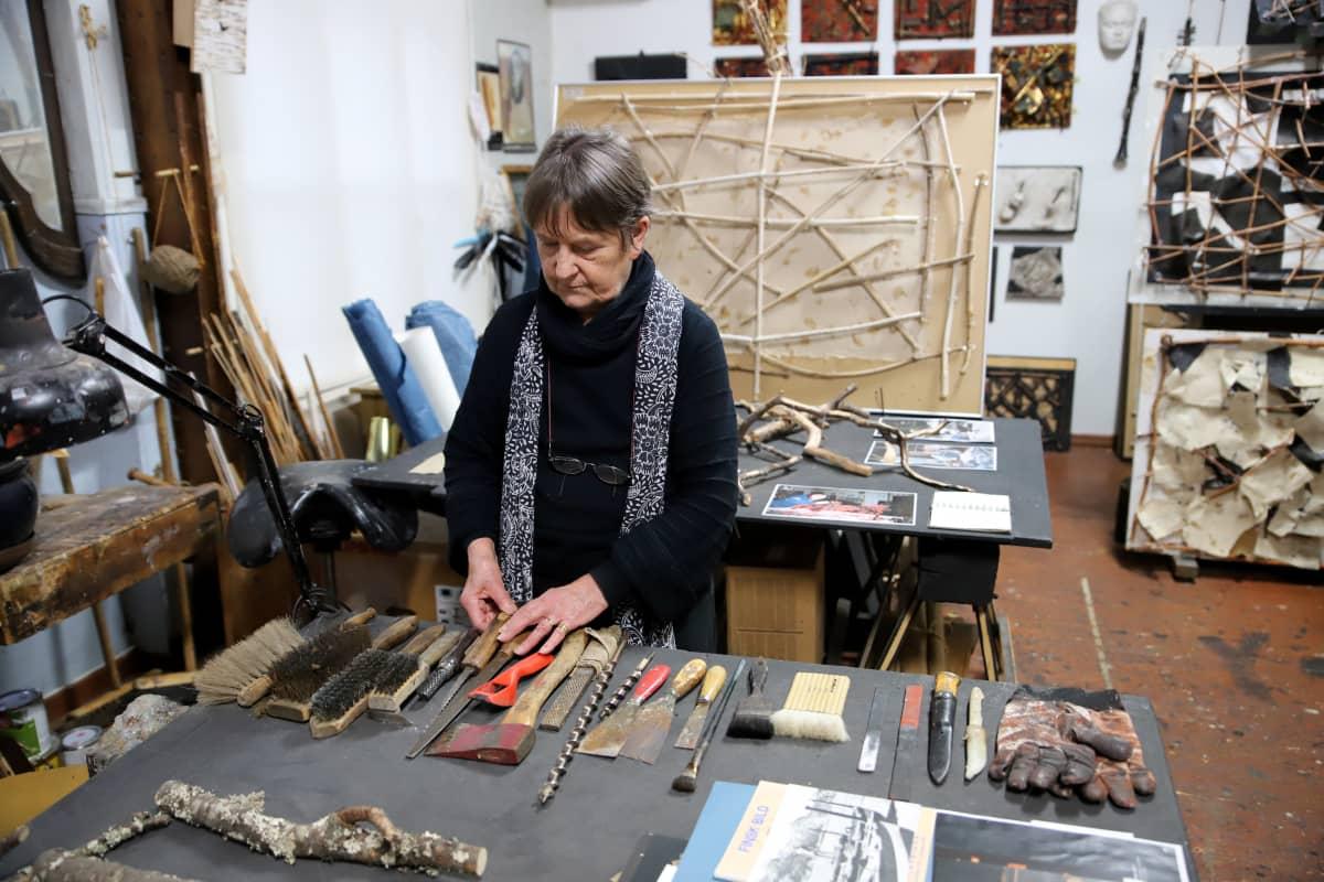 Mauno Hartmanin vaimo Pirkko Hartman työhuoneen pöydän äärellä missä Manun työkalut ovat siinä järjestyksessä kuin ne häneltä jäivät.