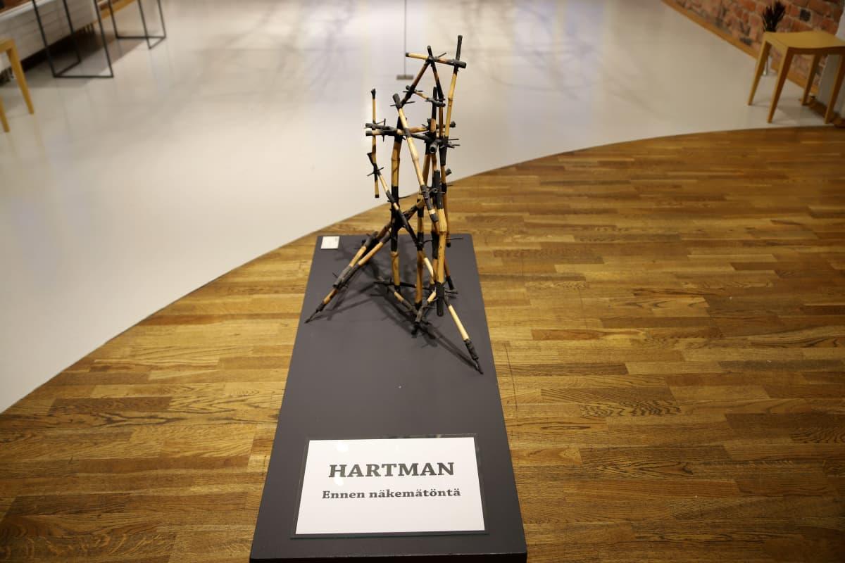 Näyttelyyn tulijaa tervehtii putkikasvista tehty veistos.