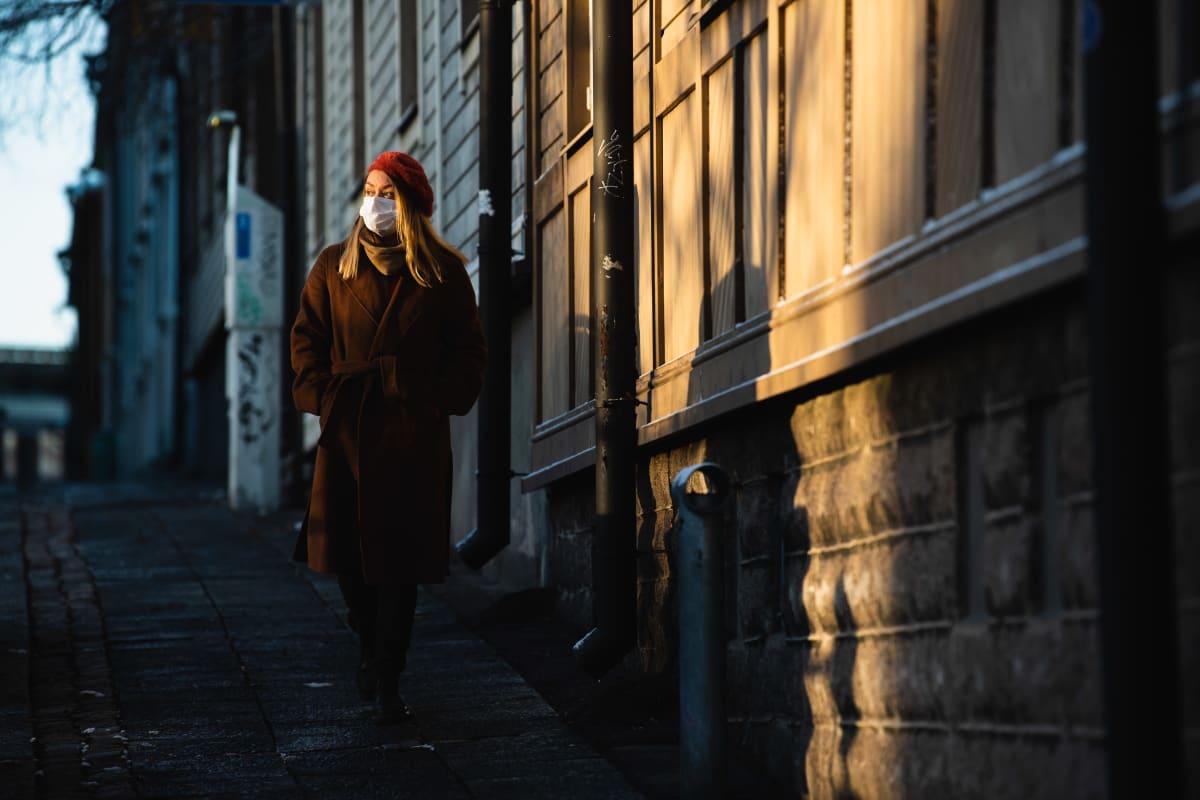 Nainen hengitysmaski kasvoilla kävelee Puu-Vallilassa.