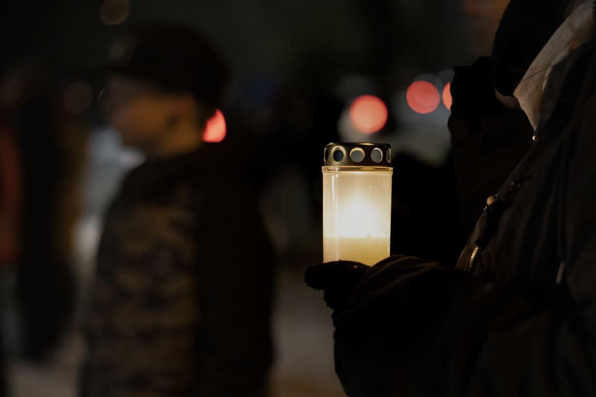 Ihmiset katsoivat mopoilijoiden muistoajo kynttilät kädessä Jyväskylässä.