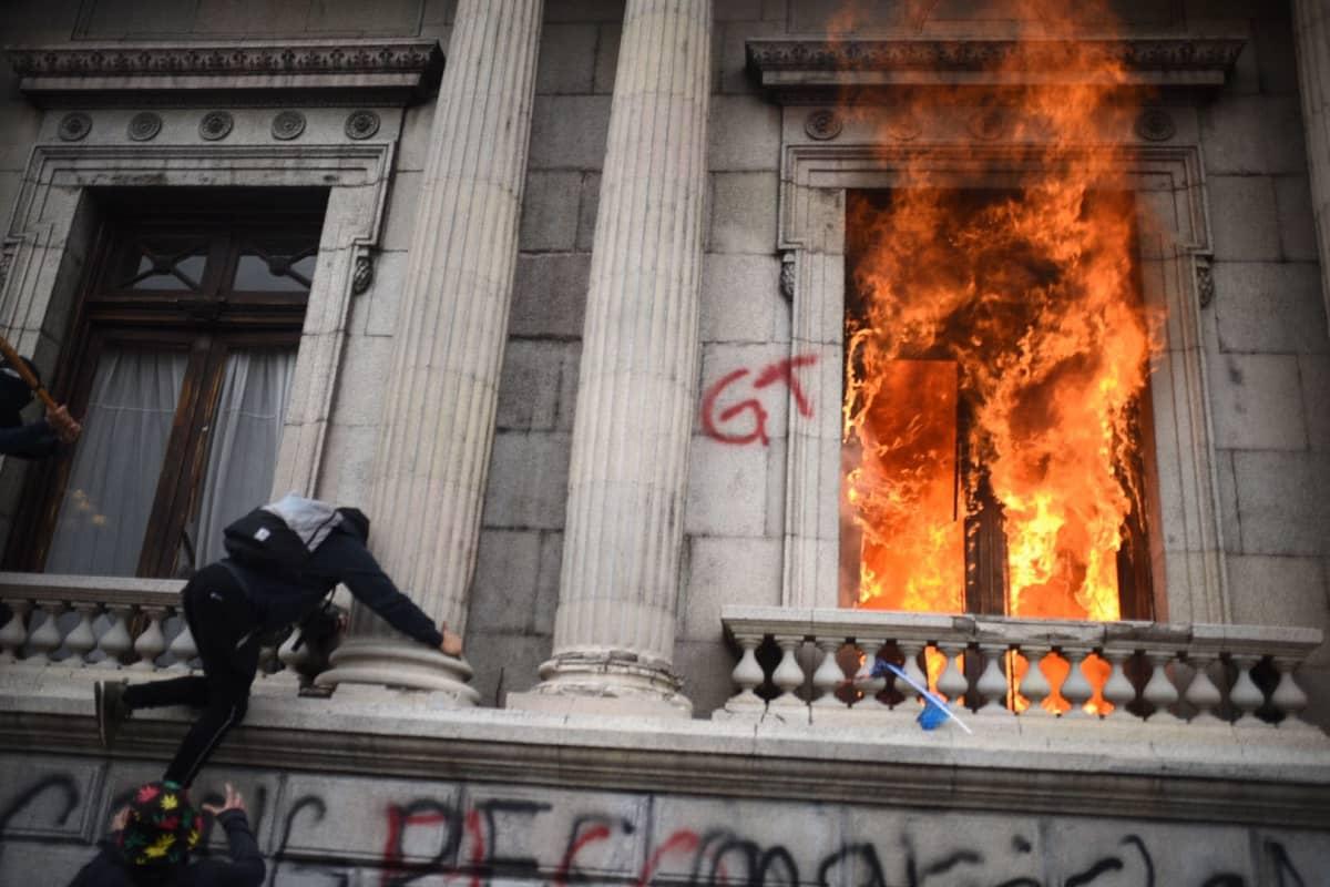 Liekit lyövät ulos ikkunasta, toiselle ikkunalle kiipeää mielenosoittaja
