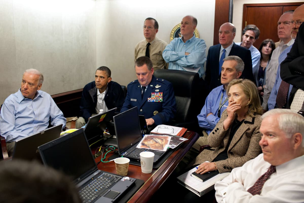 Yhdysvaltojen johtoa neuvotteluhuoneessa pöydän ääressä ja ympärillä