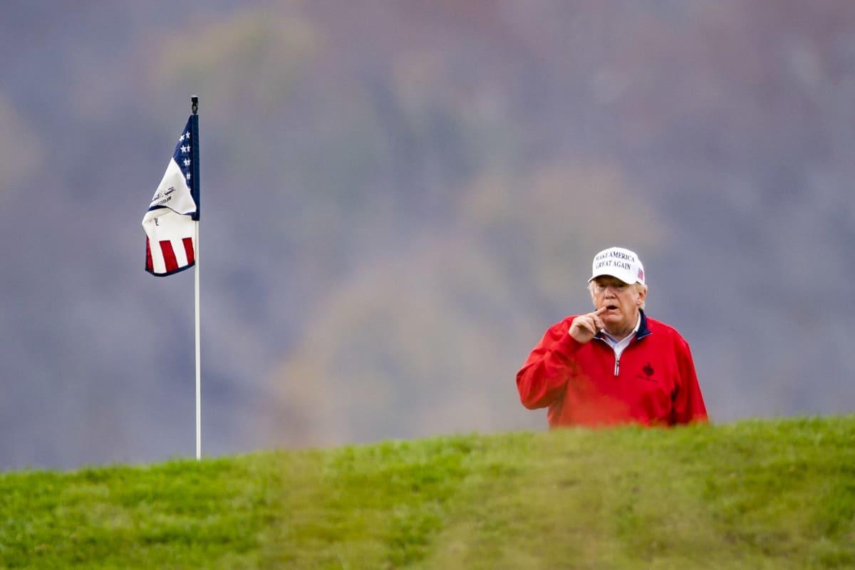 Golfia pelaava Donald Trump katselee väylää kumpareen takaa, kumpareen huipulla on USa:n lipun mallinen golf-lippu.
