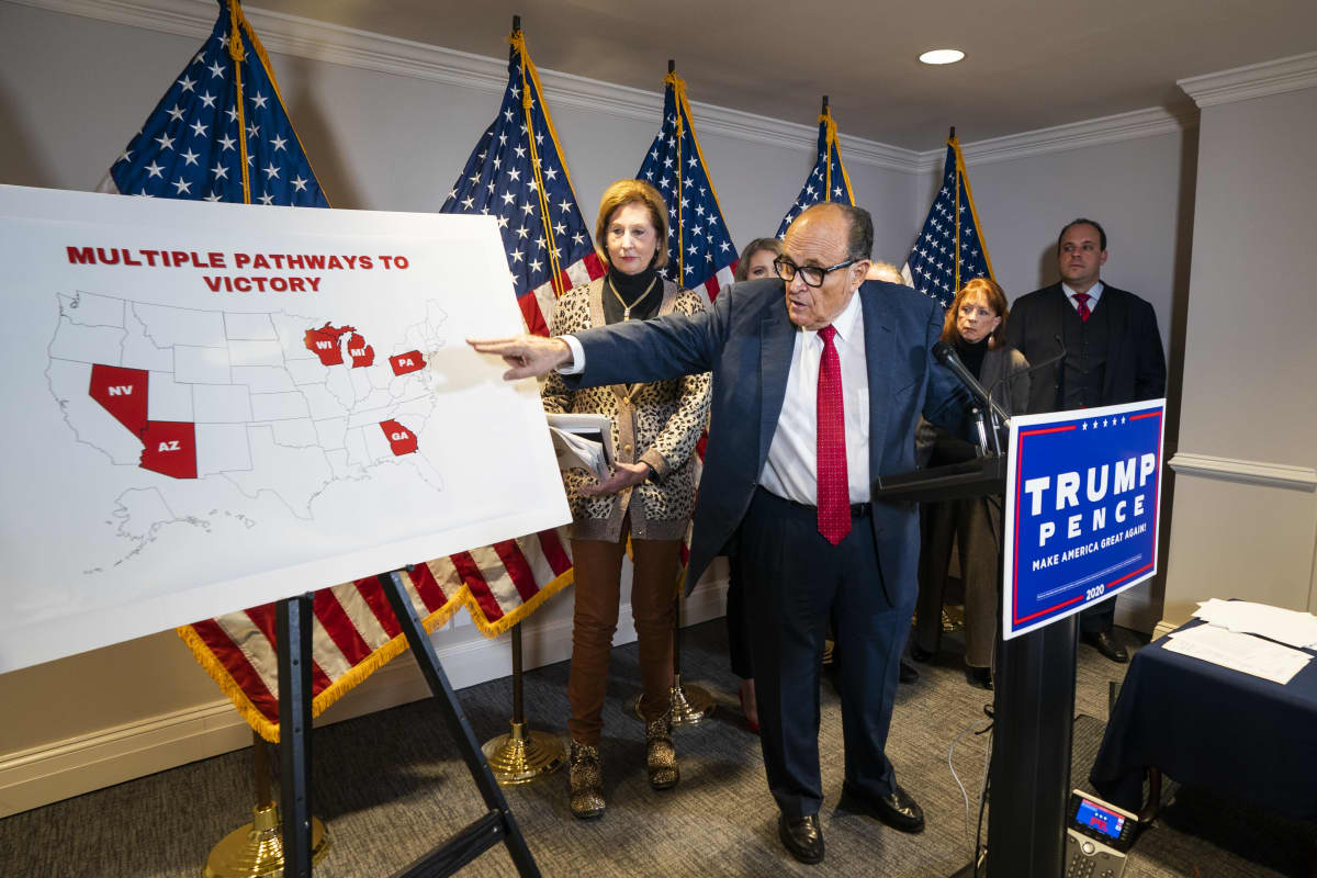 Rudy Giuliani esittelee USAn karttapohjaa, johon on merkitty punaisella joukko vaa'ankieliosavaltioita. Kartassa lukee englanniksi: multiple pahtways to victory