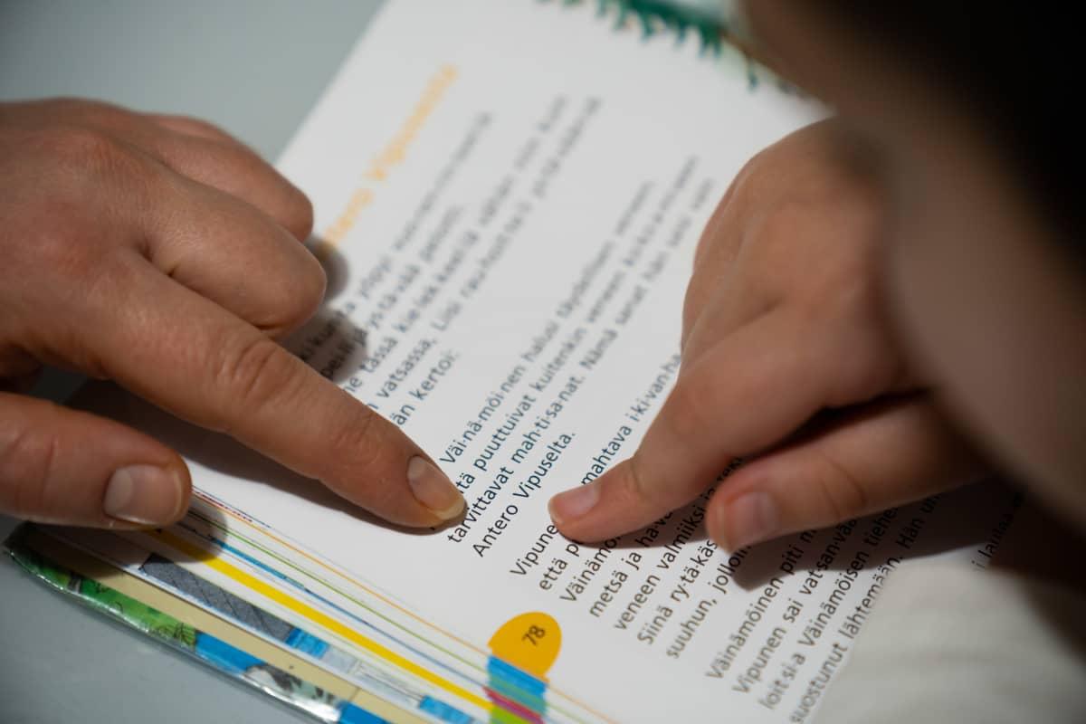 Toisen luokan äidinkielen kirjasta osoitetaan sormella mitä luetaan.
