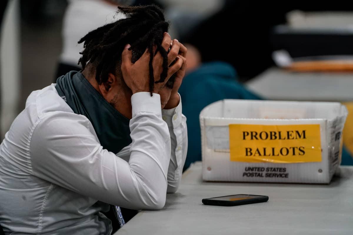 Musta ääntenlaskija nojaa väsyneenä käsiinsä ääntelaskupaikassa Detroitissa.