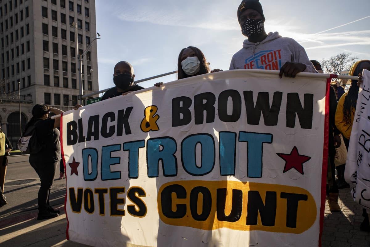 Mienosoittajat kantavat kylttiä Detroitissa. Bannerissa lukee englanniksi: Black&Brown Detroit votes count.