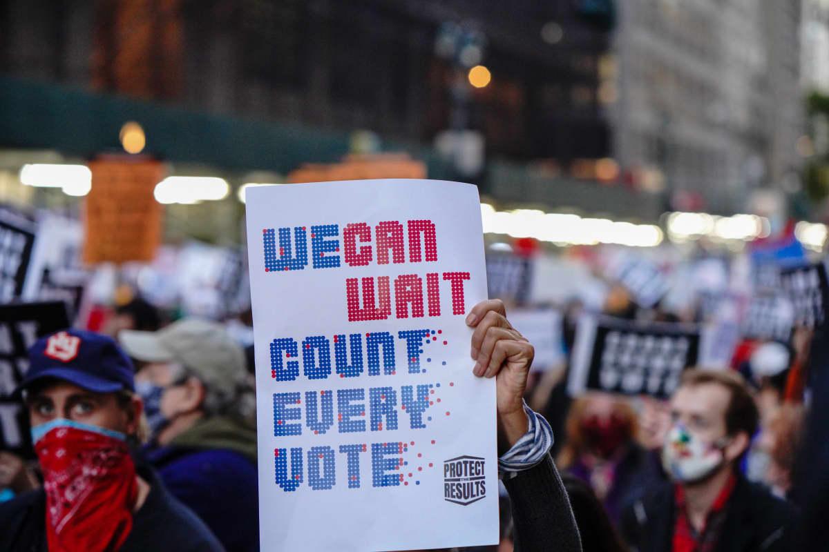 Mielenosoittaja kantaa kylttiä New Yorkissa. Plakaattiin on kirjoitettu englanniksi: We can wait. Count every vote.