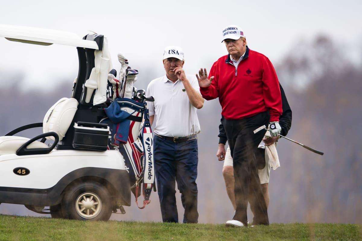 Presidentti Trump tervehtii kuvaajia golfi pelatessaan. Kuvassa vasemmalla Trumpin käytttämä golfauto.