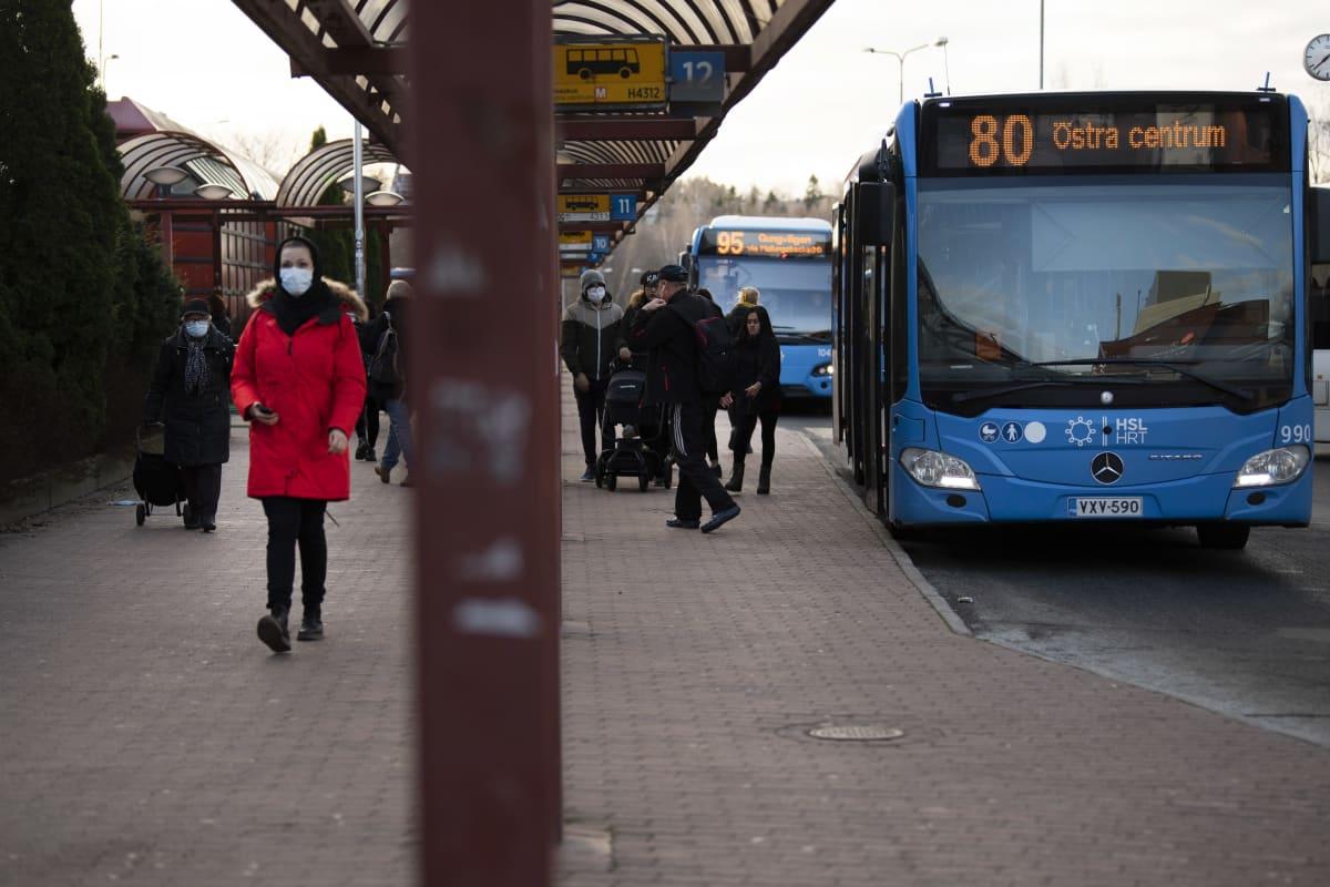 Matkustajia Itäkeskuksen bussiterminaalin edustalla.