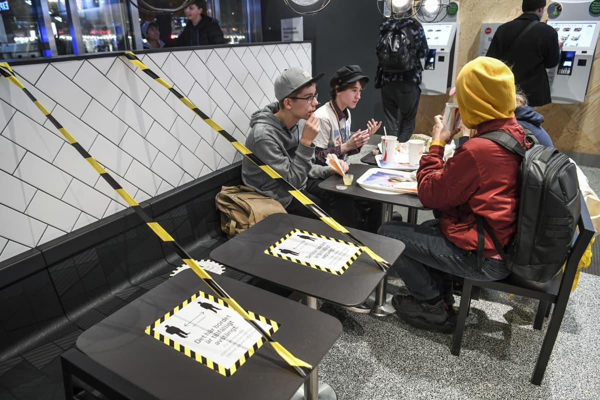 Neljä nuorta syö pikaruoka-annoksia, etualalla kaksi pöytää on eristetty varoitusteipein.
