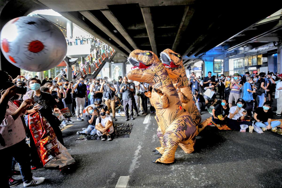 Kaksi hirmuliskoasuihin pukeutunutta mielenosoittajaa esiintyy mielenilmauksessa sillan alla. Ympärillä on nuoria mielenosoittajia.