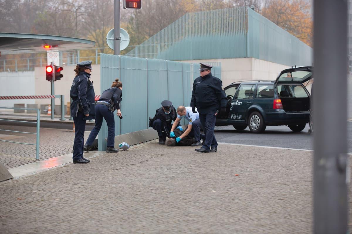 Maassa makaava mies ja poliiseja.