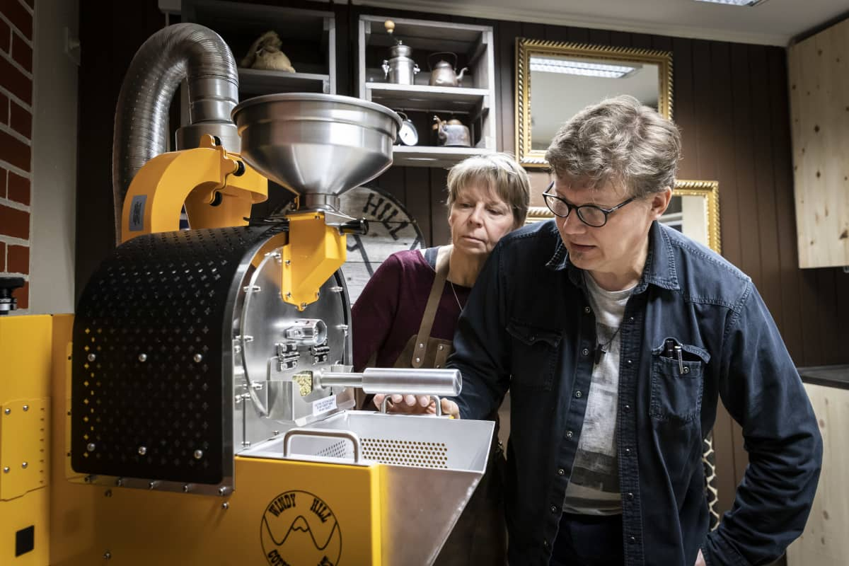 Nainen ja mies tarkkailevat kahvipaahdinta.